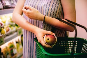 Vegan woman in supermarket putting an apple into a green basket