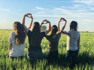 happy vegan girls with hearts in a green field