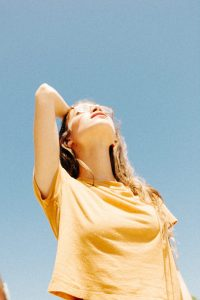 woman in yellow top looking at sun for vitamin d