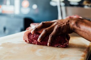 butcher with hand on slab of meat