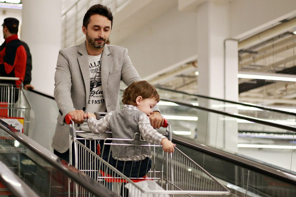 man doing first vegan shop at supermarket with child